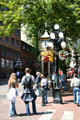 Visitors listen to whistles of Gastown Steam Clock. Vancouver, BC.
