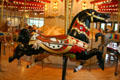 Black hunting horse with rabbit on C.W. Parker Carousel at Burnaby Village Museum. Burnaby, BC.