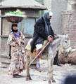 Woman with basket on head & man riding donkey in Giza. Egypt