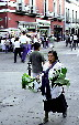Native leaf seller walks streets of Puebla. Mexico.
