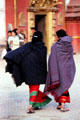 Cloaked women in front of Golden Gate in Durbar Square, Bhaktapur. Nepal.