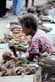 Cutting the husks off coconuts in Port Moresby market. Papua New Guinea.