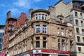 Grecian-style sandstone commercial building with chamfered corner bays. Glasgow, Scotland.