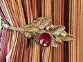 Acorn tie back on curtains made of Bohemian glass at Conde-Charlotte Museum. Mobile, AL