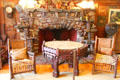 Living room fireplace with rustic octagonal table at Gillette Castle State Park. East Haddam, CT.