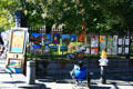 Artist displays paintings on cast iron fence of Jackson Square. New Orleans, LA.