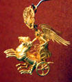 Ancient Greek gold earring of Nike driving her chariot from Peleponnesos at Museum of Fine Arts. Boston, MA.