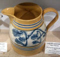 Mustard colored milk pitcher with flowing blue sponge pattern at Woodman Museum. Dover, NH