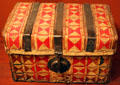 Leather petecas travel chest decorated with red bayeta wool from Mexico at New Mexico History Museum. Santa Fe, NM.