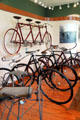 Collection of antique bicycles including Dayton Triplet on wall at Carillon Historical Park. Dayton, OH.