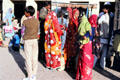 Women wearing brightly colored winter sari along the streets of Mandawa. India.